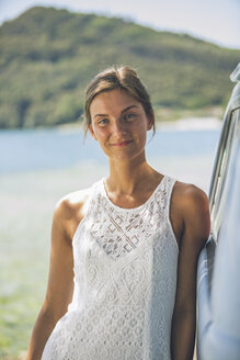 Italy, Lake Garda, portrait of smiling young woman leaning against camping bus - SBOF00296