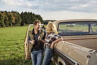 Couple at pick up truck with beer bottles - FMKF03163