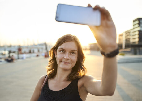 Germany, Young woman in Hamburg taking selfie with her smart phone - WHF00006