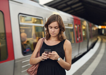 Germany, Young woman with smart phone exploring Hamburg - WHF00015