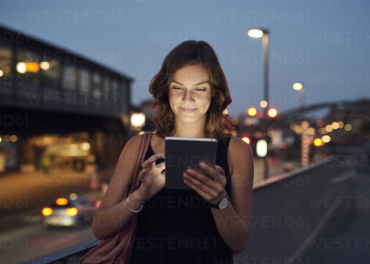 Germany, Hamburg, Young woman in the street using digital tablet - WHF00018 - Wiho/Westend61