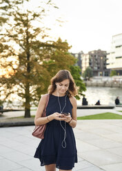 Germany, Young woman with smart phone exploring Hamburg - WHF00030