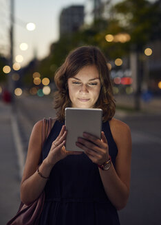 Germany, Hamburg, Young woman in the street using digital tablet - WHF00036