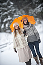 Portrait of two friends with yellow umbrella in winter - HHF05468