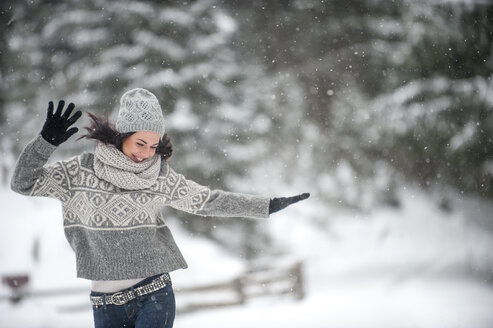 Happy woman wearing knitwear dancing in the snow - HHF05471