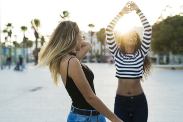 Two young women having fun on square at sunset - KKAF00013
