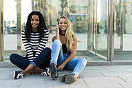 Two happy young women sitting at glass wall outdoors - KKAF00022