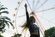 Enthusiastic young woman on a funfair with a ferris wheel - KKAF00034
