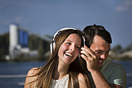 Happy young couple sharing headphones - JTLF00122