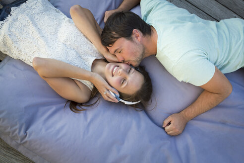 Young couple in love relaxing together on beanbag - JTLF00125
