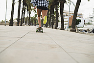 Back view of young woman skateboarding - KKAF00045