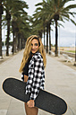 Spain, portrait of smiling young woman with skateboard - KKAF00048