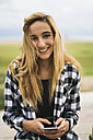 Portrait of smiling young woman with smartphone - KKAF00054