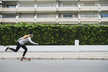 Young woman skateboarding on street - KKAF00057