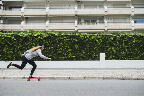 Young woman skateboarding on street - KKAF00057