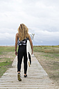Back view of young woman with surfboard on wooden boardwalk - KKAF00063