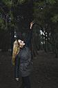 Smiling woman touching tree limb - KKAF00066