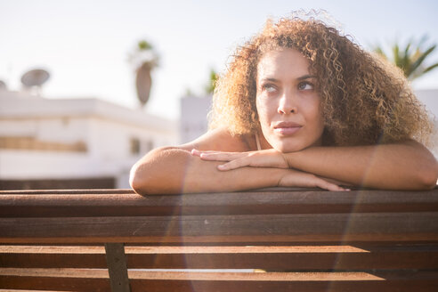 Portrait of young woman on bench at sunlight - SIPF01060