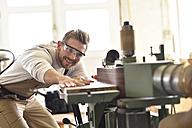Carpenter using belt sander in his workshop - LYF00665