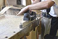 Carpenter working with plane in workshop - LYF00671