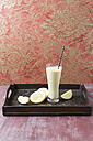 Glass of banana smoothie with apple and lemon on wooden board - MYF01833