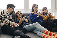 Four friends with smartphones on couch in living room hanging out - LCUF00081