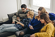 Four friends with smartphones on couch in living room hanging out - LCUF00084