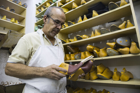 Shoemaker selecting shoe lasts from a shelf in his workshop - ABZF01484