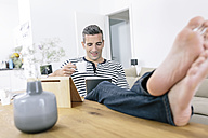 Relaxed man at home using tablet - MADF01181