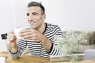 Smiling man at home holding coffee cup - MADF01184