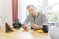 Man at home with camera and tablet - MADF01193