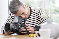 Man at home checking camera - MADF01196