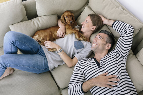 Smiling couple with dog lying on couch - MADF01199