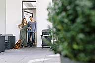 Smiling couple with dog standing at terrace door - MADF01202