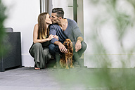Couple with dog kissing at terrace door - MADF01205