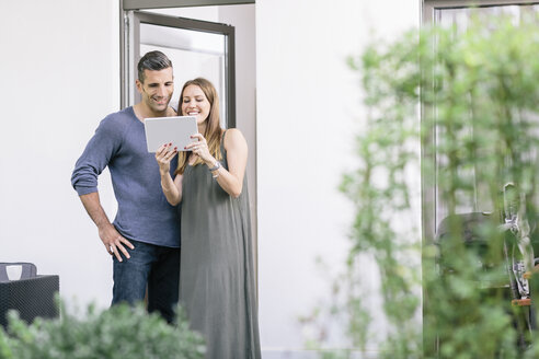 Smiling couple at terrace door sharing tablet - MADF01208