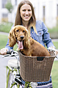 Smiling woman with dog in bicycle basket - MADF01211