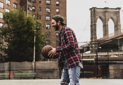 USA, New York, laughing young man with basketball on an outdoor court - UUF09125