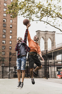 USA, New York, two young men playing basketball on an outdoor court - UUF09128