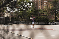 Young man playing basketball on an outdoor court - UUF09131
