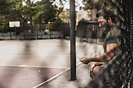 Young man with cell phone and basketball on an outdoor court - UUF09137