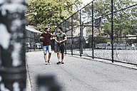 Two friends walking with basketball outdoors - UUF09140