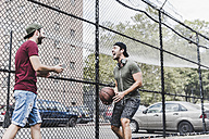 Two young men with basketball having fun on an outdoor court - UUF09146