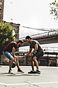 USA, New York, two young men playing basketball on an outdoor court - UUF09149