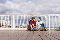 USA, New York City, two friends sitting on bridge on Coney Island - UUF09167