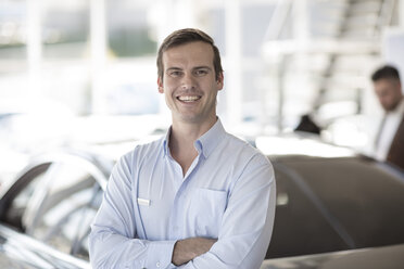Portrait of smiling car dealer in showroom - ZEF11539