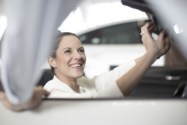 Smiling woman sitting in car at car dealership - ZEF11545