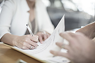 Woman signing contract at desk at car dealership - ZEF11554