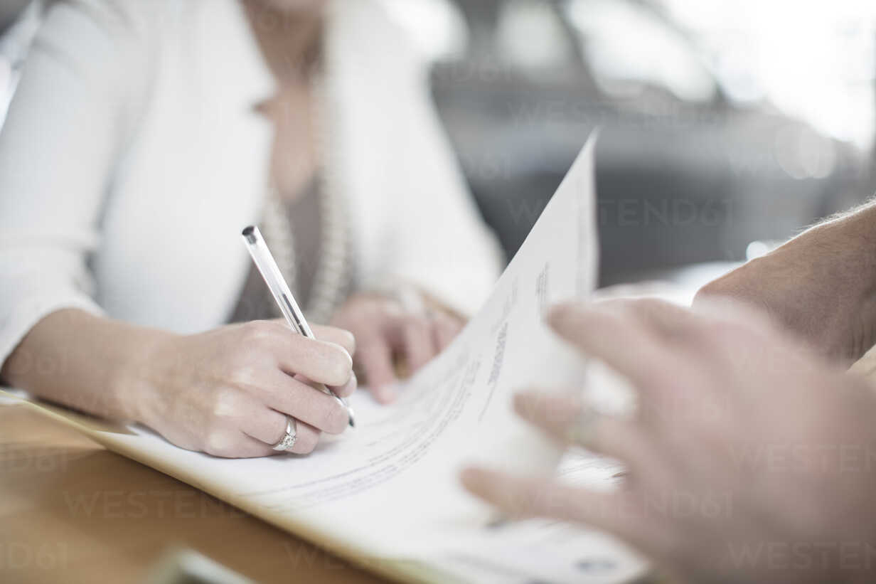 Woman signing contract at desk at car dealership - ZEF11554 - zerocreatives/Westend61