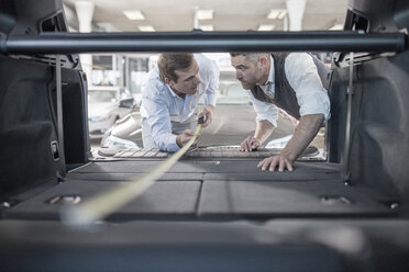 Car dealer measuring trunk of car at car dealership - ZEF11566